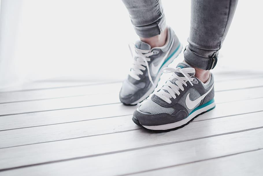 A person wearing grey and turquoise Nike trainers stands on a grey wooden floor