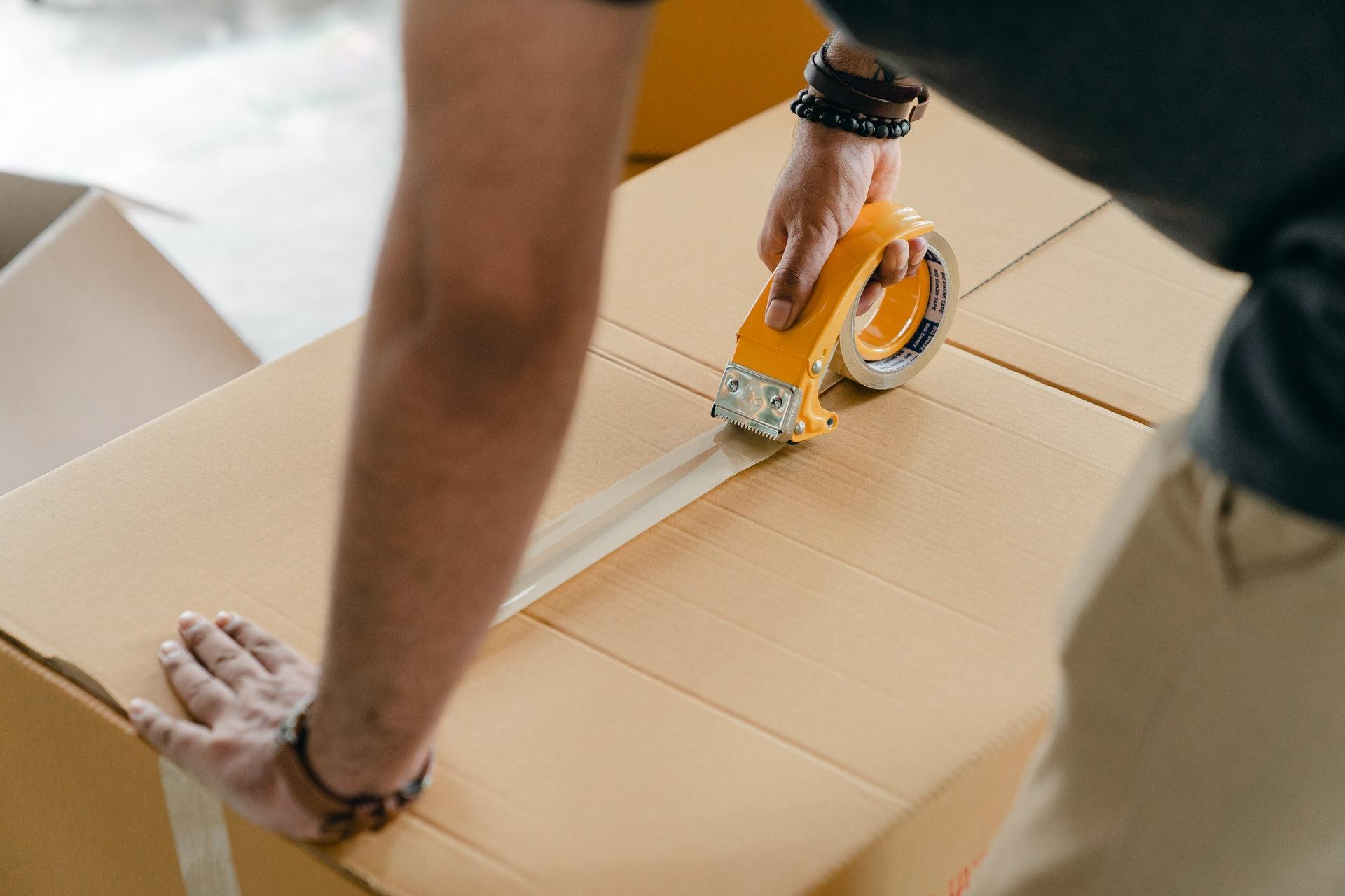 A man taping up an ecommerce order to be shipped to customers.