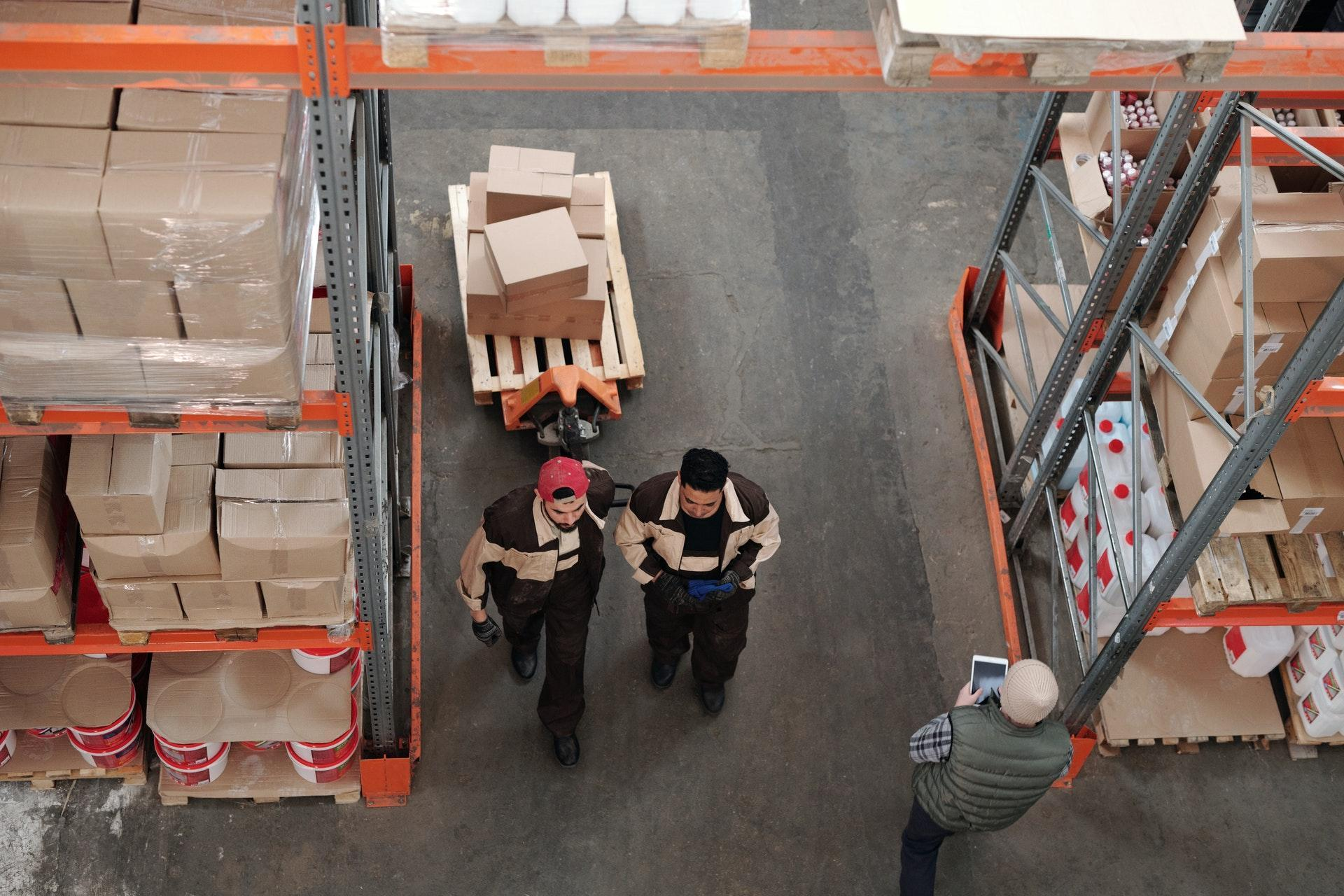 Two men in a warehouse fulfilling dropshipping orders for an ecommerce store.